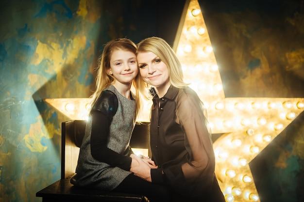 Stylowa blondynka mama i córka w czarne ubrania na tle gwiazd ze światłami.