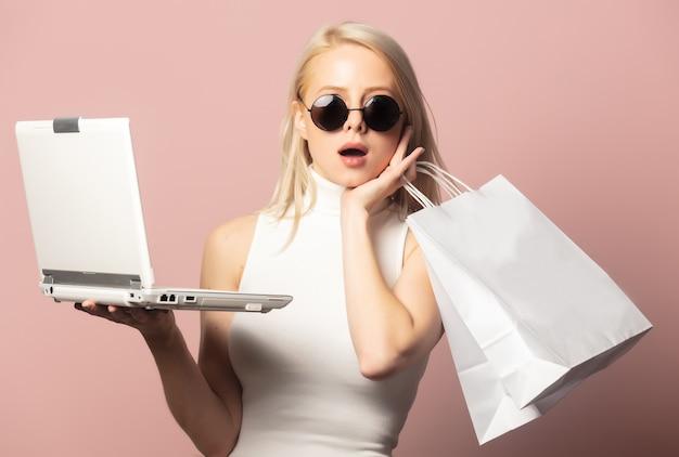 Stylowa blondynka na górze z torbami na zakupy i notatnikiem na różowo