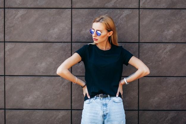 Stylowa blondynka na sobie czarną koszulkę i okulary pozuje na ulicy