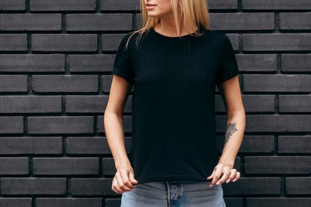 Stylowa blondynka na sobie czarną koszulkę, pozowanie na tle czarnej ściany