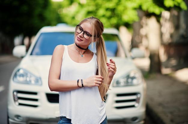 Stylowa blondynka noszą dżinsy, okulary, naszyjnik i białą koszulę przeciwko luksusowemu samochodowi