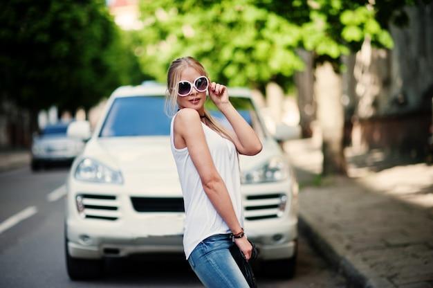 Stylowa blondynka noszą dżinsy, okulary przeciwsłoneczne, dławik i białą koszulę przeciwko luksusowemu samochodowi