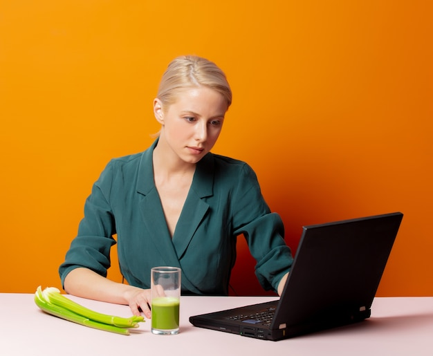 Stylowa blondynka siedzi przy stole obok soku z selera i laptopa
