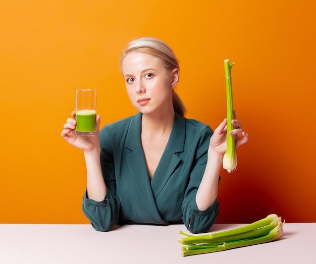 Stylowa blondynka siedzi przy stole obok soku z selera