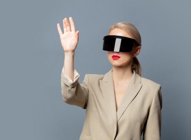 Stylowa blondynka w futurystycznych okularach vr na szarej przestrzeni