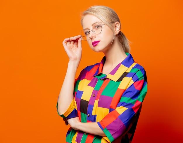Stylowa blondynka w koszuli z lat 90. i okularach na pomarańczowo