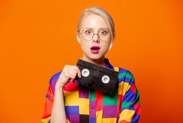 Stylowa blondynka w koszuli z lat 90. i okularach typu vhs na pomarańczowo