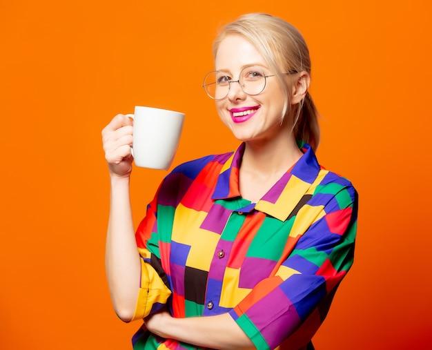 Stylowa blondynka w koszuli z lat 90. i okularach z pomarańczową filiżanką