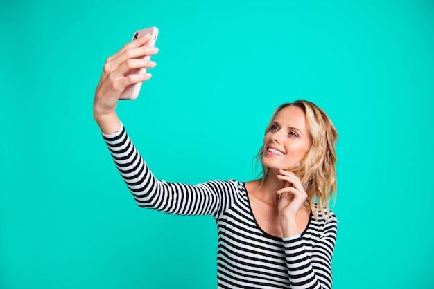 Stylowa blondynka w pasiastym swetrze pozuje na niebieskiej ścianie