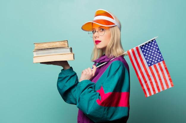 Stylowa blondynka w sportowym garniturze z lat 90. z książkami i flagą usa