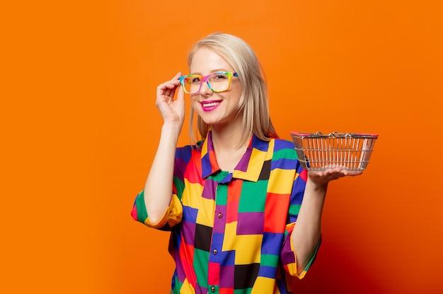 Stylowa blondynka w ubraniach z lat 90. z pomarańczowym koszem na zakupy