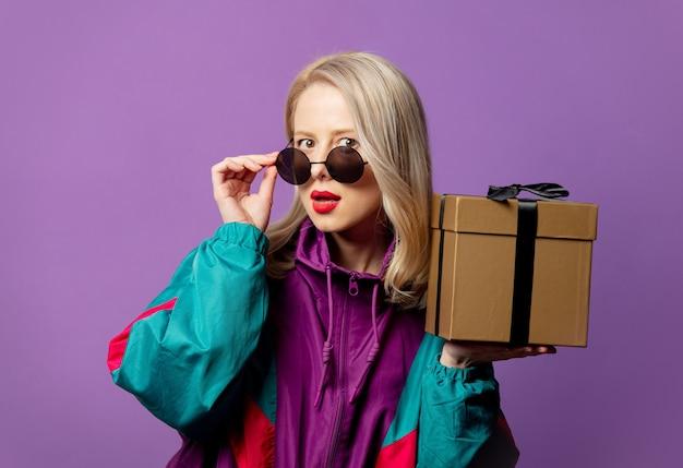 Stylowa blondynka w wiatrówce z lat 80. i okrągłych okularach przeciwsłonecznych w pudełku na fioletowej ścianie