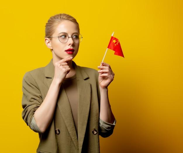 Stylowa blondynki kobieta w kurtce z chińczyk flaga na kolorze żółtym