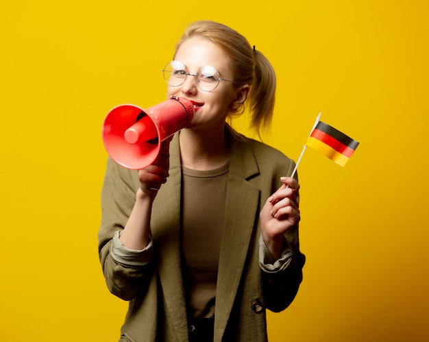Stylowa blondynki kobieta w kurtce z niemiec flaga i megafonem na kolorze żółtym