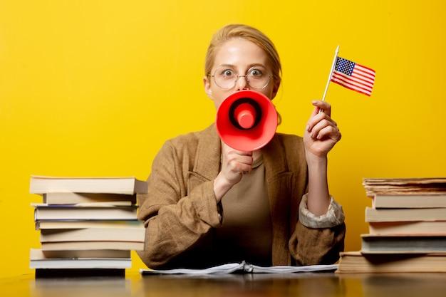 Stylowa blondynki kobieta w obsiadaniu przy stołem z usa flaga i megafonem z książkami wokoło na kolorze żółtym