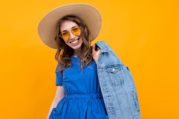 Stylowa brązowowłosa kobieta w żółtych okularach i niebieskiej sukience na tle żółtej ściany