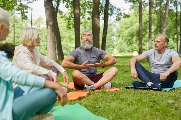 Stylowa brodata trenerka jogi siedząca na macie, pokazująca swoim starszym klientom, jak ćwiczyć oddech