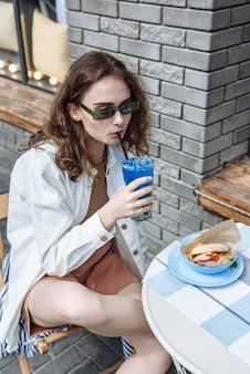 Stylowa brunetka kobieta w okularach pijąca koktajl w restauracji siedząca przy stole portret