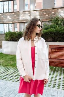 Stylowa brunetka kobieta w okularach pozuje w nowej kolekcji ubrań katalogu mody