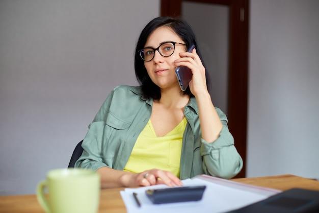 Stylowa brunetka kobieta w okularach siedzi przy drewnianym stole z notatnikiem i po telefon w nowoczesnym miejscu pracy