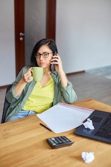 Stylowa brunetka kobieta w okularach siedzi przy drewnianym stole z notatnikiem i po telefonie, pije herbatę w nowoczesnym miejscu pracy