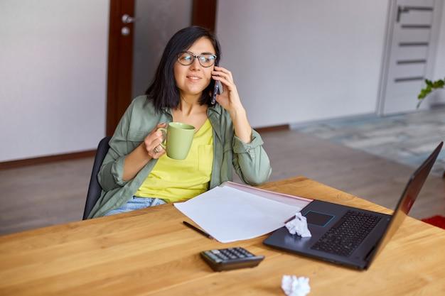 Stylowa brunetka kobieta w okularach siedzi przy drewnianym stole z notatnikiem i po telefonie