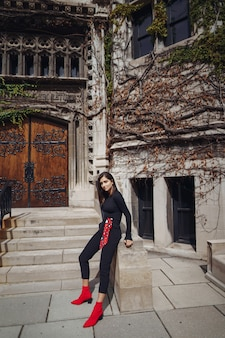 Stylowa brunetka stoi obok entance do budynku