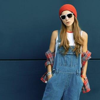 Stylowa brunetka w czerwonej czapce i denimie w miejskich lokalizacjach
