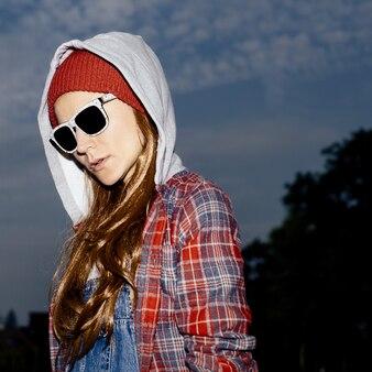 Stylowa brunetka w czerwonej czapce i modnych ubraniach w miejskich lokacjach