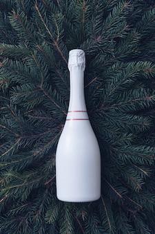 Stylowa, całkowicie biała, nieoznakowana, zakorkowana butelka szampana na łóżku z zielonych liści sosny na boże narodzenie, nowy rok, specjalne okazje lub koncepcje uroczystości