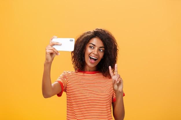 Stylowa ciemnoskóra kobieta z kręconymi fryzurami pokazująca gest pokoju podczas robienia selfie.