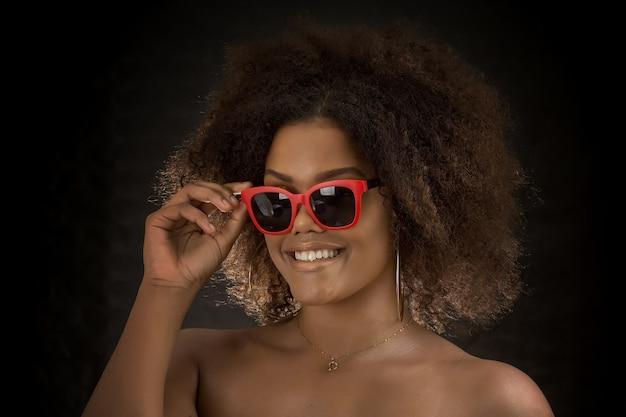 Stylowa czarna kobieta w czerwonych okularach przeciwsłonecznych