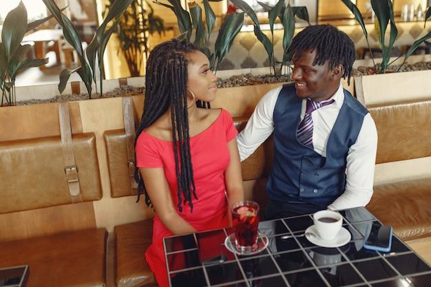 Stylowa czarna para siedzi w kawiarni i pije kawę