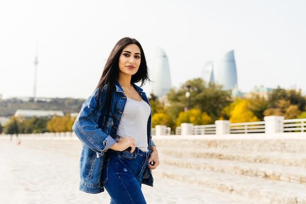 Stylowa czarnowłosa dziewczyna podróżuje po azerbejdżanie, spaceruje po mieście baku