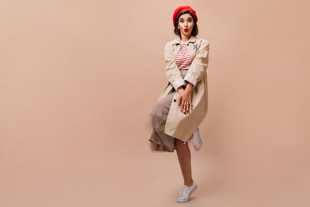 Stylowa dama w okopie i kapeluszu nieśmiało pozuje na beżowym tle. śliczna dziewczyna w swetrze w paski, beżowym płaszczu i skoczkach w czerwonym berecie.