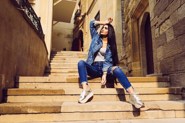 Stylowa długowłosa dziewczyna podróżuje na wakacje, siedzi na schodach na świeżym powietrzu w mieście baku