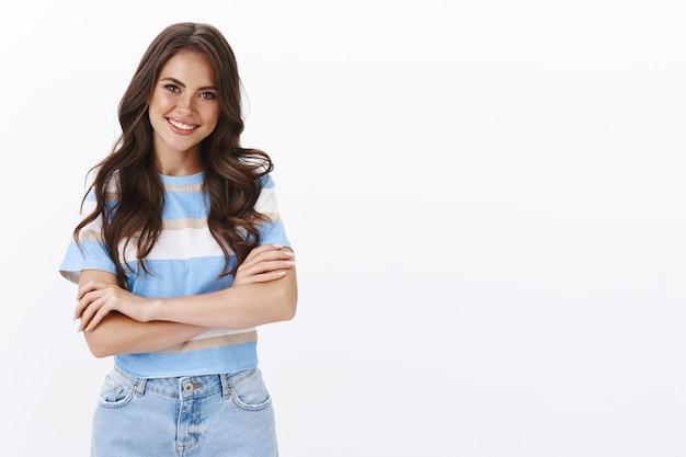 Stylowa, dobrze wyglądająca ambitna uśmiechnięta brunetka z kręconą fryzurą, skrzyżowanymi rękami w klatce piersiowej pewna profesjonalna poza, uśmiechnięta stojąca niedbale letnim stroju, rozmawiająca z przyjacielem biała ściana