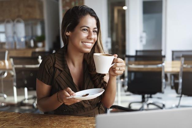 Stylowa, dobrze wyglądająca pani biurowa, ciesząc się gorącą kawą, trzymając kubek w samej kawiarni