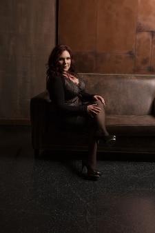 Stylowa dojrzała brunetka w modnym stroju pozuje na skórzanej sofie w ciemnym pokoju