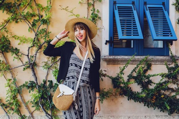 Stylowa dorywczo elegancka kobieta w słomkowym kapeluszu i czarnej kurtce pozuje na ulicy