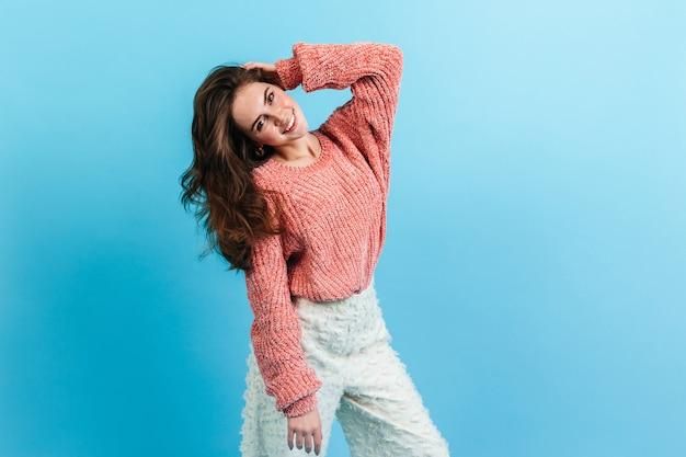 Stylowa dziewczyna dotyka jej falujących długich włosów. portret kobiecej damy w niezwykłych spodniach i różowym swetrze.