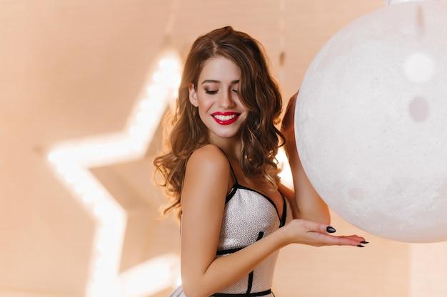 Stylowa dziewczyna dotyka ogromnej białej zabawki świąteczne. zadowolona młoda kobieta patrzy w dół z uśmiechem, pozuje przed świecącą gwiazdą.