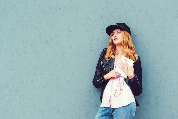 Stylowa dziewczyna hipster słuchać muzyki na zewnątrz. kobieta w hełmofonach i używać pastylkę nad szarości ścianą. koncepcja mody, technologii i ludzi.