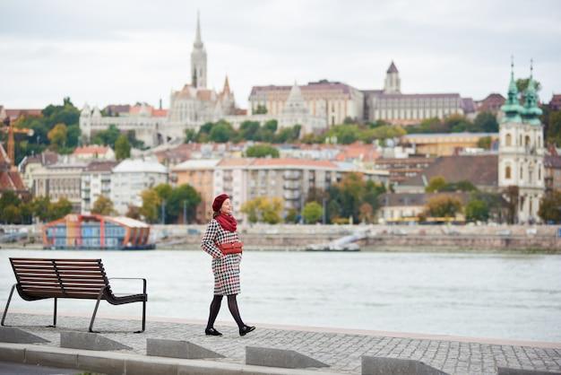 Stylowa dziewczyna idzie wzdłuż nabrzeża budapesztu z niewyraźnym widokiem na stronę budy