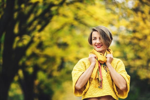 Stylowa dziewczyna jesienią w żółtym swetrze i szaliku