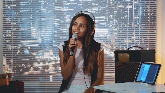 Stylowa dziewczyna mieszanej rasy śpiewa do mikrofonu na próbie w domowym studio