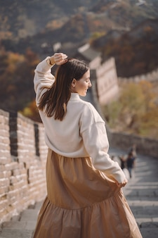Stylowa dziewczyna odwiedza wielki mur chiński w pobliżu pekinu w sezonie jesiennym.