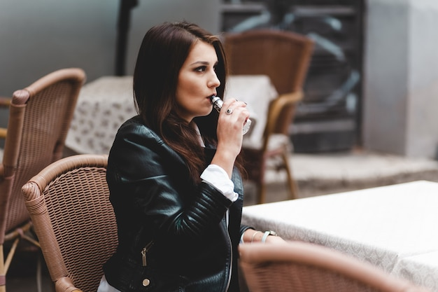 Stylowa dziewczyna pali elektroniczny papieros. poważna kobieta z vape obsiadaniem na stole