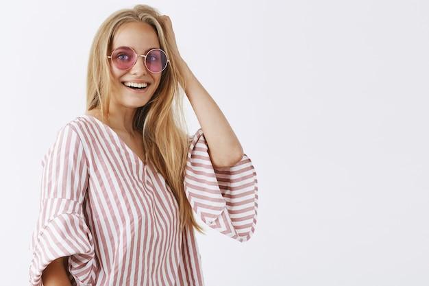 Stylowa dziewczyna pozuje na białej ścianie z okularami przeciwsłonecznymi