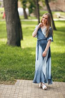 Stylowa dziewczyna pozuje w sukience w słonecznym wiosennym parku